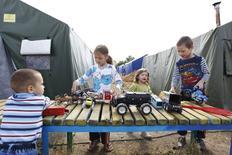 Дети играют во временном лагере для беженцев в Ростовской области 22 июня 2014 года. Около 16.400 человек покинули дома на востоке Украины за истекшую неделю, жалуясь на боевые действия, угрозы, похищения и разрушение инфраструктуры социальных услуг, что довело общую численность временно перемещенных лиц в стране до 54.000, сообщило в пятницу Агентство ООН по делам беженцев. REUTERS/Eduard Korniyenko