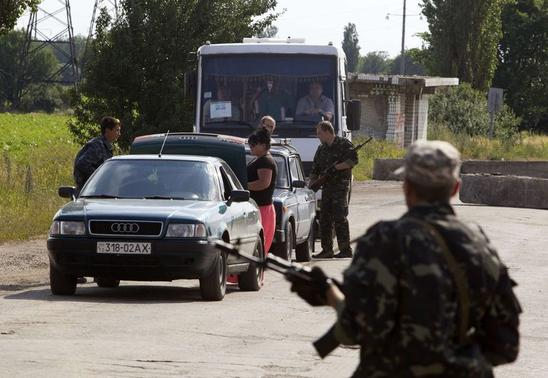 Pro-Russian separatists inspect vehicles at a road checkpoint outside the town of Lysychansk in the Luhansk region of eastern Ukraine, June 24, 2014. REUTERS/Shamil Zhumatov