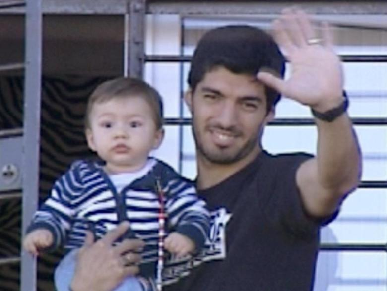 Uruguayan striker Luis Suarez carries his son Benjamin as he waves to supporters from the balcony of his house in the small coastal town of Solymar, in the outskirts of Montevideo in this June 27, 2014 still image taken from footage provided by Television Nacional Uruguay via Reuters TV.  REUTERS/Television Nacional Uruguay (TNU)/Handout via Reuters TV
