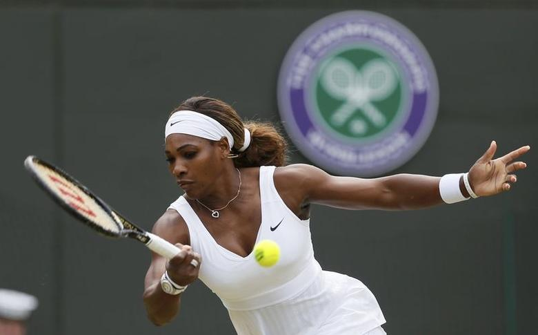 Serena Williams of the U.S. hits a return to Alize Cornet of France during their women's singles tennis match at the Wimbledon Tennis Championships, in London June 28, 2014.     REUTERS/Stefan Wermuth