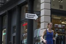 A woman walks past an American Apparel store in New York June 19, 2014.  REUTERS/Brendan McDermid
