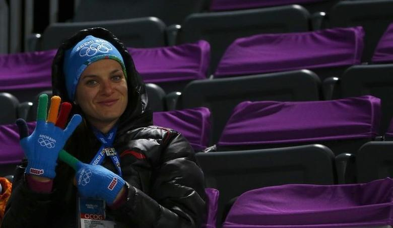Olympic pole vault champion Yelena Isinbayeva sits in the tribune during second jump of the men's ski jumping large hill individual qualification round at the Sochi 2014 Winter Olympics, February 14, 2014. REUTERS/Michael Dalder