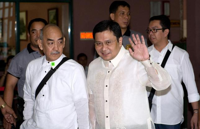 Senator Jose 'Jinggoy' Estrada (C), son of former Philippine President Joseph Estrada , waves as he arrives at the graft court for his arraignment in Manila June 30, 2014. REUTERS/Noel Celis/Pool
