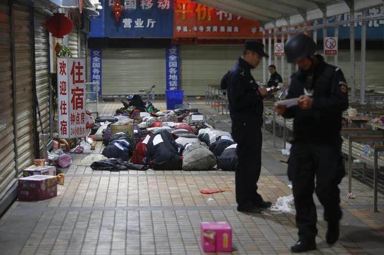 Policemen check unclaimed luggage at a square outside the Kunming railway station after a knife attack, in Kunming, Yunnan province March 2, 2014. REUTERS/Stringer
