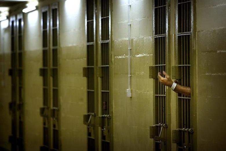 An Iraqi detainee gestures toward U.S. soldiers through bars of his cell at Abu Ghraib prison outside Baghdad May 17, 2004.REUTERS/Damir Sagolj