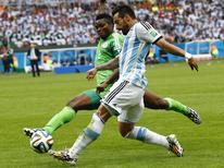 Jogador da Nigéria Joseph Yobo disputa bola com Ezequiel Lavezzi, da Argentina, durante partida no Estádio Beira-Rio, em Porto Alegre. 25/6/2014 REUTERS/Stefano Rellandini