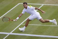 Stanislas Wawrinka of Switzerland hits a return during his men's singles tennis match against Feliciano Lopez of Spain at the Wimbledon Tennis Championships, in London July 1, 2014.            REUTERS/Suzanne Plunkett