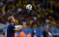 Técnico da seleção dos EUA, Juergen Klinsmann, arremessa a bola durante o jogo contra a Bélgica pelas oitavas de final da Copa do Mundo, no estádio Fonte Nova, em Salvador. 1/06/2014. REUTERS/Marcos Brindicci