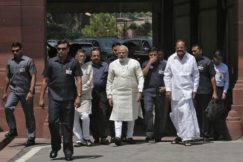 Prime Minister Narendra Modi (C) walks to speak with the media as he arrives to attend his first Parliament session in New Delhi June 4, 2014. REUTERS/Adnan Abidi