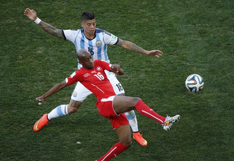 Argentina's Marcos Rojo fights for the ball with Switzerland's Gelson Fernandes (R) during their 2014 World Cup round of 16 game at the Corinthians arena in Sao Paulo July 1, 2014. REUTERS/Paulo Whitaker