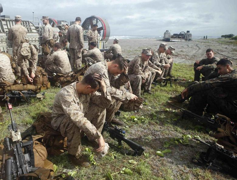 U.S. marines of 1st Battalion, 8th Marines Regiment rest during the Cooperation Afloat Readiness and Training (CARAT) Philippines 2014, a U.S.-Philippines military exercise, on a beach facing South China sea, at San Antonio, Zambales north of Manila June 30, 2014. REUTERS/Erik De Castro
