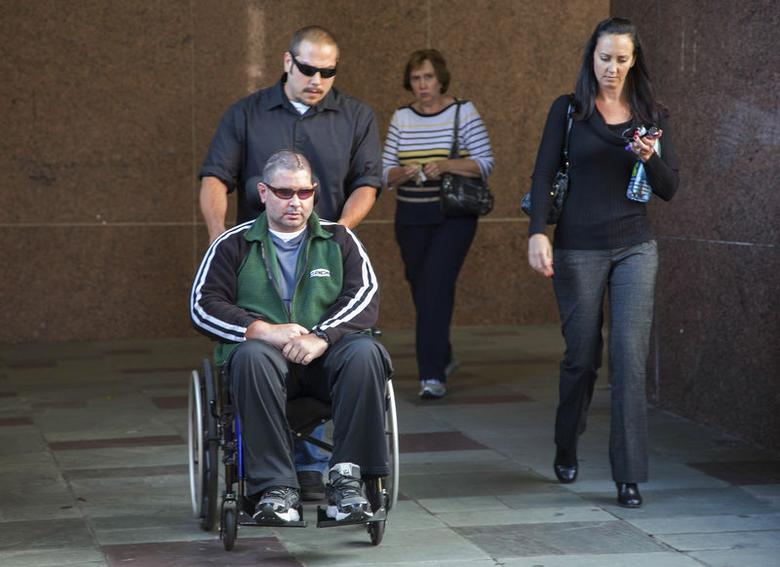 San Francisco Giants fan Bryan Stow (L on wheelchair) leaves a Los Angeles Court with his sister Bonnie Stow (R) and his mother Ann Stow (2nd R)  the day before closing arguments in a civil trial in a lawsuit brought by Stow against former Los Angeles Dodgers owner Frank McCourt in Los Angeles, California June 25, 2014.  REUTERS/Lucy Nicholson