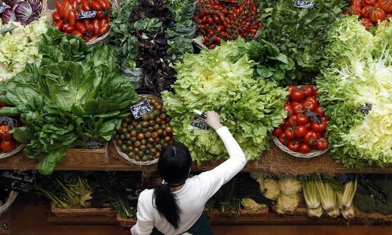 An employee arranges pricetags at a vegetables work bench during the opening day of upmarket Italian food hall chain Eataly's flagship store in downtown Milan, March 18, 2014. REUTERS/Alessandro Garofalo
