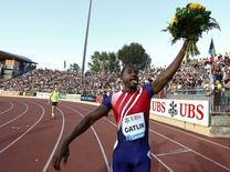 Justin Gatlin of the U.S. raises a bouquet of flowers after winning the men's 100m race during the Lausanne Diamond League meeting at the Stade de la Pontaise in Lausanne July 3, 2014.        REUTERS/Denis Balibouse