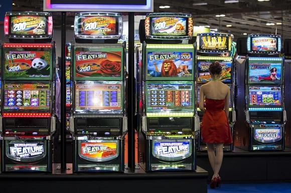 A visitor tries a slot machine during the Global Gaming Expo Asia in Macau May 20, 2014. REUTERS/Tyrone Siu/Files