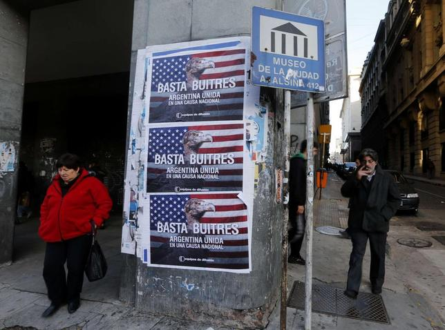 Pedestrians stand next to posters that read ''Enough vultures, Argentina united for a national cause'' in Buenos Aires June 18, 2014.  REUTERS/Enrique Marcarian
