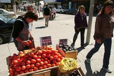 La dueña de un puesto de verduras y frutas vende sus productos en la calle, después de que su tienda fuera destruida en Talcahuano, 24 de marzo de 2010. La inflación en Chile habría llegado a un 0,2 por ciento en junio, impulsado por alzas en los precios de alimentos y del transporte público, aunque contrarrestado por bajas en los rubros de vestuario y gas licuado. REUTERS/Jose Luis Saavedra