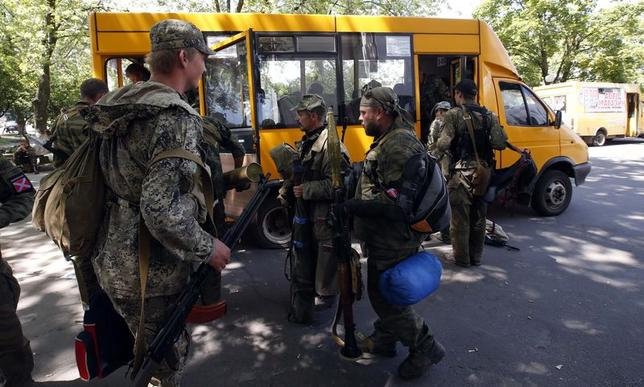 Armed pro-Russian separatists board a bus as they leave their positions in Kramatorsk in eastern Ukraine July 5, 2014. Pro-Russian rebels were pulling out of a flashpoint area of eastern Ukraine on Saturday as authorities in Kiev savoured a major military success in its three-month fight against the separatists. A Reuters reporter saw a convoy of around 20 military transport vehicles and buses filled with armed rebels driving out of Kramatorsk where they had gone after apparently earlier fleeing the separatist stronghold of Slaviansk nearby. REUTERS/Maxim Zmeyev (UKRAINE - Tags: POLITICS CIVIL UNREST MILITARY) - RTR3X88R