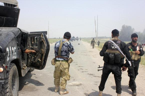 Iraqi security forces and armed volunteers move with military vehicles during clashes with militants of the Islamic State, formerly known as the Islamic State in Iraq and the Levant (ISIL), in the town of Dalli Abbas in Diyala province July 3, 2014. REUTERS/Stringer