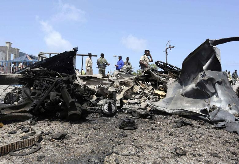 Somali government soldiers gather near the wreckage after a suicide car explosion near the Somali parliament building in Mogadishu July 5, 2014. REUTERS/Feisal Omar