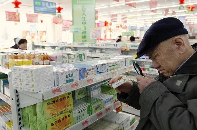 An elderly man uses a magnifier to see the descriptions on a pack of medicine at a pharmacy in Dandong, Liaoning province March 30, 2011. REUTERS/Jacky Chen/Files