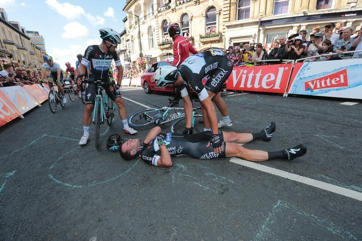 Omega Pharma-Quick Step team rider Mark Cavendish of Britain gets assistance after crashing during a mass sprint next to the finish line of the first 190.5 km stage of  the Tour de France cycling race from Leeds to Harrogate, July 5, 2014.     REUTERS/Fred Mons/Pool