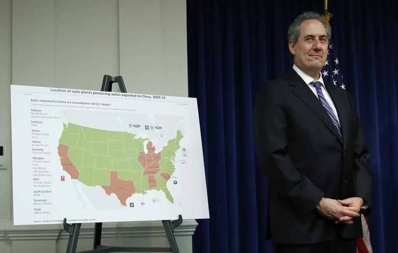 U.S. Trade Representative Michael Froman stands beside a map showing locations of auto plants that export to China during a news conference at the USTR in Washington May 23, 2014.   REUTERS/Kevin Lamarque