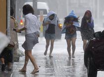 Женщины идут по улице в Наха, провинция Окинава 8 июля 2014 года. Сотни авиарейсов отменены, более 500.000 человек должны покинуть свои дома из-за мощного тайфуна, ударившего по юго-западной части Японии сильным ветром и ливнями и ожидающегося в Токио в течение недели. REUTERS/Kyodo
