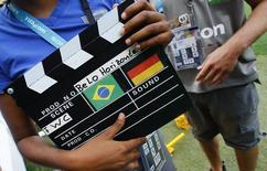 """Член съемочной бригады держит режиссерскую хлопушку с флагами Бразилии и Германии во время тренировки немецкой сборной на стадионе """"Минейран"""" в Белу-Оризонти 7 июля 2014 года. Бразилия сыграет с Германией в полуфинале чемпионата мира в ночь на среду в городе Белу-Оризонти. REUTERS/Kai Pfaffenbach"""