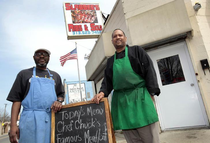 Kevin Ward (L) and Charlie Monagan, co-owners of Slabbee's Ribs & Soul, stand in front of their recently opened take-out rib joint in Detroit, Michigan April 17, 2013. REUTERS/Rebecca Cook