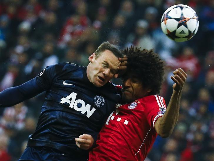 Manchester United's Wayne Rooney goes for a header with Bayern Munich's Dante (R) during their Champions League quarter-final second leg soccer match in Munich, April 9, 2014.      REUTERS/Kai Pfaffenbach