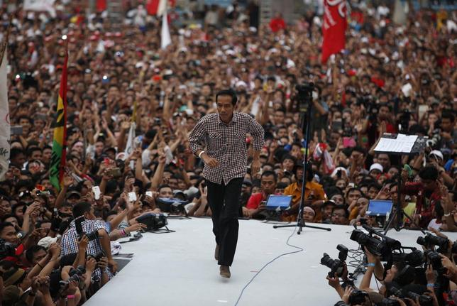 Indonesian presidential candidate Joko ''Jokowi'' Widodo runs on the stage after delivering a speech in front of his supporters at Gelora Bung Karno stadium in Jakarta July 5, 2014.  REUTERS/Darren Whiteside