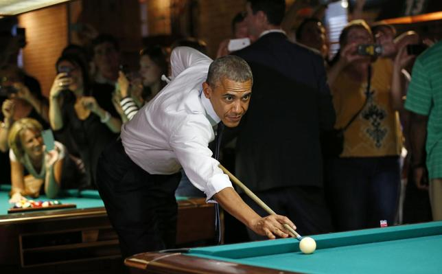 U.S. President Barack Obama shoots pool during a stop in a bar in Denver July 8, 2014.  Obama will speak about the economy at an event in Denver tomorrow. REUTERS/Kevin Lamarque