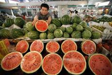 Продавец раскладывает арбузы на прилавке на рынке в городе Хуайбэй в провинции Аньхой 10 июня 2014 года. Потребительская инфляция в Китае замедлилась немного сильнее, чем ожидалось, в июне, указывая на сохраняющуюся слабость экономики. REUTERS/Stringer