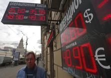Мужчина у пункта обмена валют в Москве, 20 февраля 2014 года. Рубль в среду вышел на июльские пики за счет закрытия длинных валютных позиций локальными игроками на фоне отсутствия негативной динамики на востоке Украины, из-за спроса на высокодоходные российские активы со стороны нерезидентов, а также продаж экспортной выручки без задержки и привязки к налоговым датам. REUTERS/Maxim Shemetov