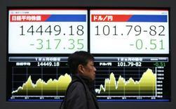 Мужчина у брокерской конторы в Токио, 20 февраля 2014 года. Азиатские фондовые рынки снизились в среду, пока инвесторы ждут квартальные результаты компаний. REUTERS/Yuya Shino