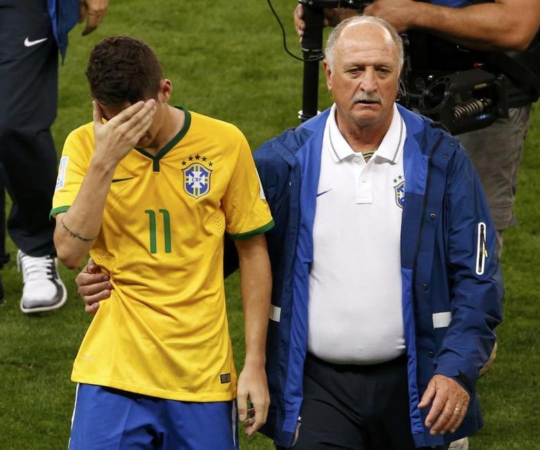 Brazil's Oscar (L) is comforted by coach Luiz Felipe Scolari after they lost their 2014 World Cup semi-finals against Germany at the Mineirao stadium in Belo Horizonte July 8, 2014.   REUTERS/David Gray