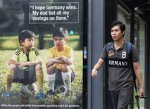 Homem passa por cartaz de campanha contrária à realização de apostas, em Cingapura, que tem lutado para coibir a prática. 9/7/2014  REUTERS/Edgar Su