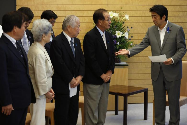Japan's Prime Minister Shinzo Abe (R) receives a petition from members of abduction issue groups at his official residence in Tokyo July 4, 2014.  REUTERS/Issei Kato