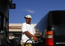 Водитель заправляет машину на заправке  Express Gas Plus в Финиксе, Аризона 10 августа 2011 года. Цены на нефть снижаются, так как слабый спрос на бензин в США сильнее повлиял на рынок, чем рост импорта нефти в Китае. REUTERS/Joshua Lott