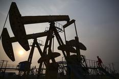 Рабочий осматривает станки-качалки PetroChina в Паньцзине 30 июня 2014 года. Китай повысил импорт нефти на 10,2 процента в первом полугодии по сравнению с прошлым годом, несмотря на слабый рост потребления нефти, что говорит о пополнении запасов. REUTERS/Sheng Li