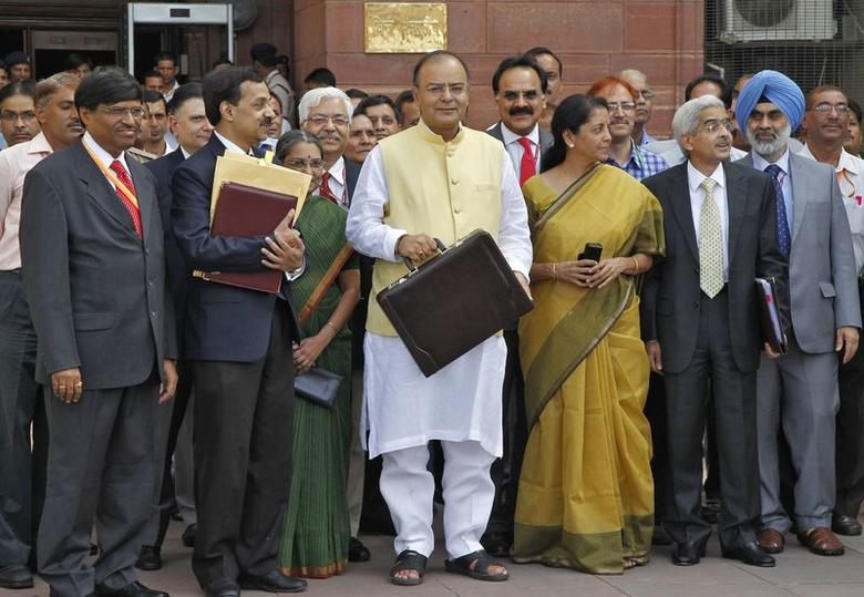 Finance Minister Arun Jaitley (C) poses as he leaves his office to present the federal budget for the 2014/15 fiscal year, in New Delhi July 10, 2014. REUTERS/Stringer