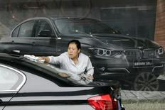 Женщина моет автомобиль BMW возле салона компании в Пекине 14 августа 2012 года. Американские управляющие фондов развивающихся рынков обращают все меньше внимания на то, где располагается или зарегистрирована компания, и все больше на то, каким образом компания делает деньги - как игрок развитого рынка, работающий в развивающемся мире, или же иным способом. REUTERS/Jason Lee