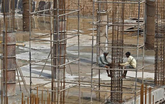 Labourers work at the construction site of a multi-level parking in Chandigarh July 10, 2014. REUTERS/Ajay Verma