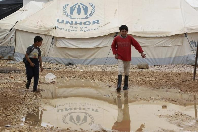 Young Syrian refugees walk near a puddle during rainy weather at Al Zaatari refugee camp in the Jordanian city of Mafraq, near the border with Syria, March 13, 2014.  REUTERS/Muhammad Hamed