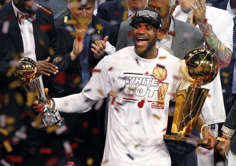 LeBron James holds the Larry O'Brien Trophy and the Bill Russell MVP trophy after the Heat defeated the Spurs to win Game 7 of the NBA Finals in 2013. REUTERS/Joe Skipper
