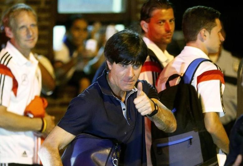 Germany's national soccer team coach Joachim Loew (2ndL) gives a thumbs-up before boading a bus in the town of Santa Cruz Cabralia, north of Porto Seguro, July 11, 2014.  REUTERS/Arnd Wiegmann