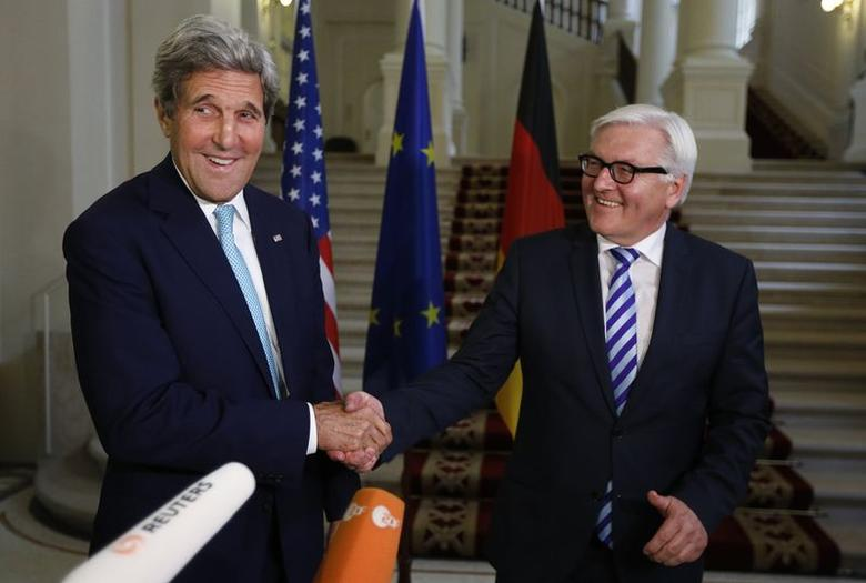 U.S. Secretary of State John Kerry (L) and German Foreign Minister Frank-Walter Steinmeier shake hands as they conclude remarks to the media, after talks between the foreign ministers of the six powers negotiating with Tehran on its nuclear program, in Vienna July 13, 2014.  REUTERS/Jim Bourg