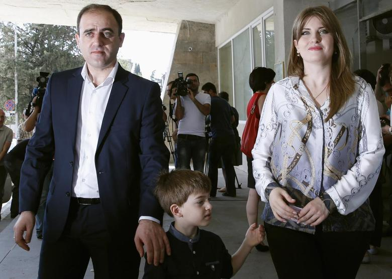 David Narmania, a mayoral candidate from Georgia's ruling Georgian Dream coalition, leaves a polling station with wife Tinatin and 5-year-old son Koko during the second round of the local election in Tbilisi, July 12, 2014. REUTERS/David Mdzinarishvili