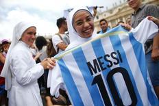 Freira na Praça São Pedro, no Vaticano, segura camisa de Lionel Messi, à espera do jogo final entre Alemanha e Argentina. 13/7/2014 REUTERS/Tony Gentile
